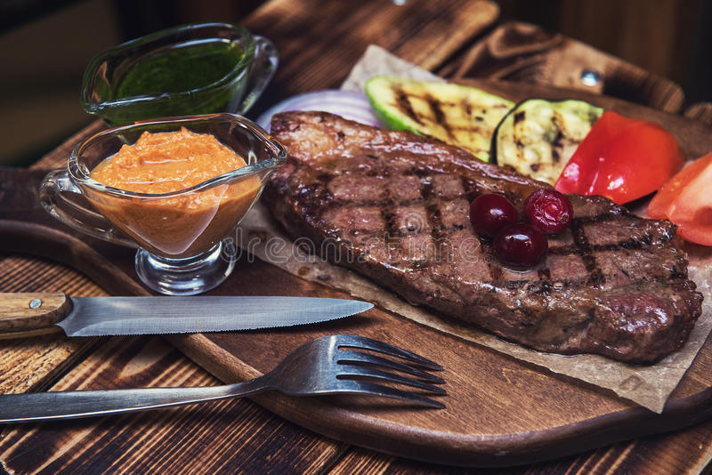 Grilled beef steak. With sauce and vegetables royalty free stock images