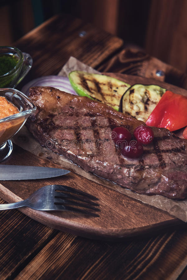 Grilled beef steak. With sauce and vegetables royalty free stock photos