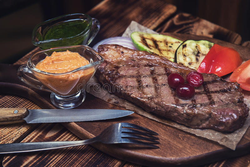 Grilled beef steak. With sauce and vegetables stock image