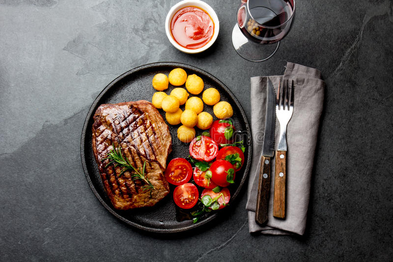Grilled beef steak served on cast iron plate with tomato salad, potatoes balls and red wine. Barbecue, bbq meat beef. Tenderloin. Top view, slate background stock photos