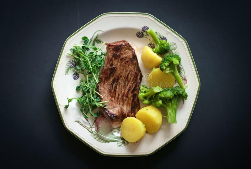 Grilled beef steak with steam potatoes and broccoli on white plate. Over black stone table. Top view royalty free stock image