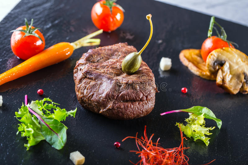 Grilled Beef steak with vegetable decoration. Grilled porterhouse steak on slate board. stock photography