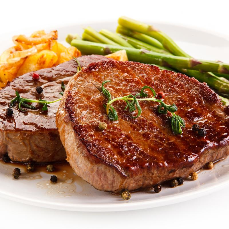 Grilled beef steaks,chips and asparagus. On white background stock photography