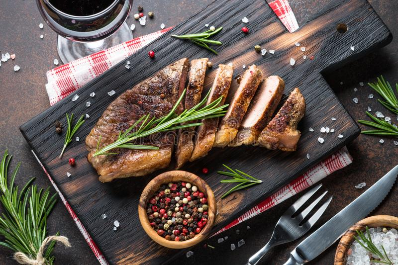 Grilled beef striploin steak with red wine glass. royalty free stock images