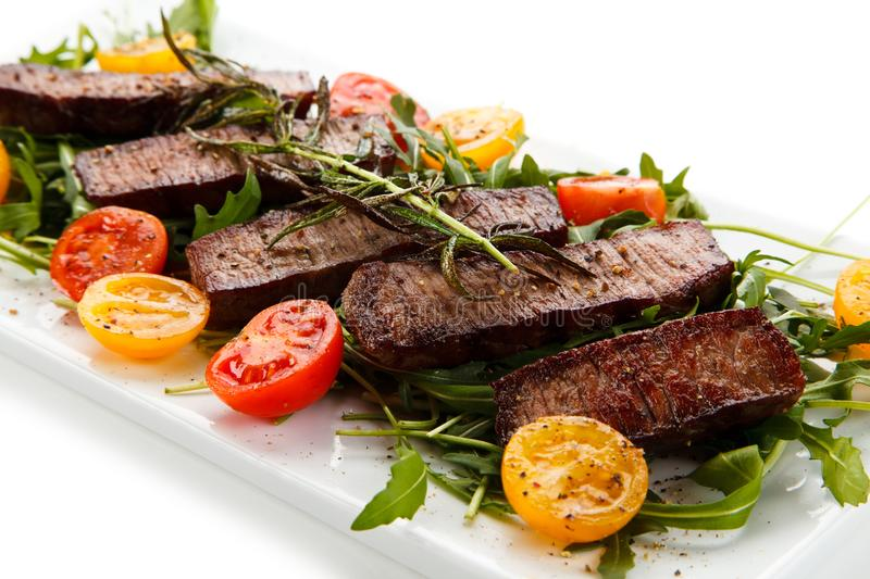 Grilled beefsteak with vegetables. On white background royalty free stock photos