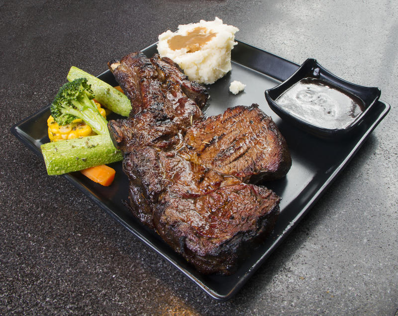 Grilled Black Angus Steak Ribeye on black plate stock photos