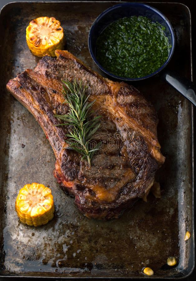 Grilled Black Angus Steak Ribeye with rosemary and corn on iron royalty free stock image