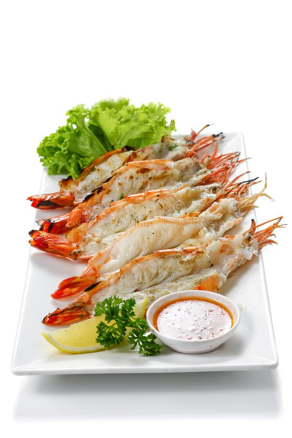 Grilled 5 black tiger shrimps with boiled potatoes, slice of lime, tomato fresh vegetables and chili seafood sauce on white square royalty free stock image
