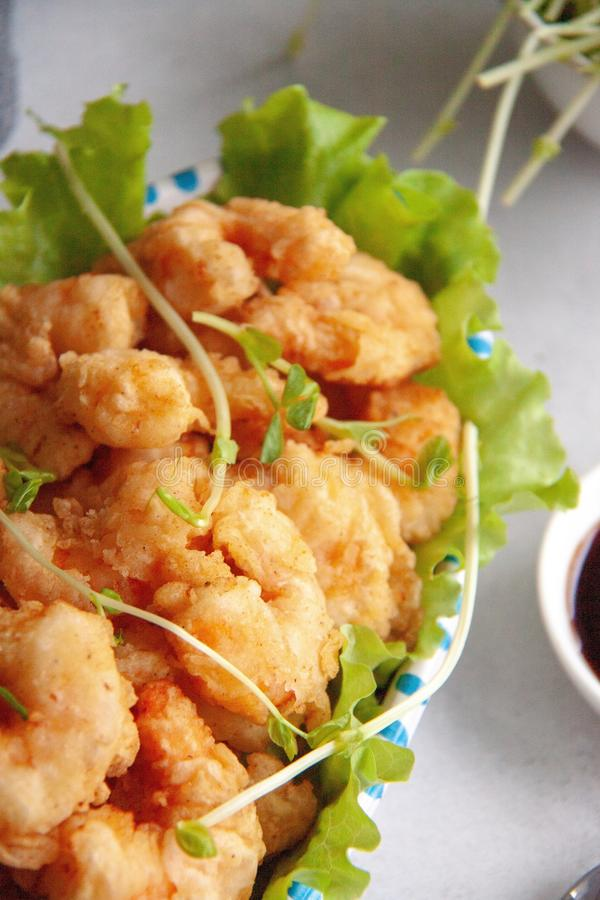 Breaded shrimp. Grilled breaded king prawns on a fresh green salad leaf royalty free stock photos