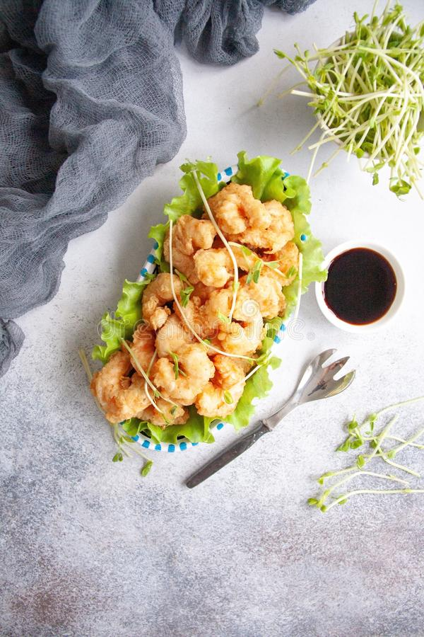 Breaded shrimp. Grilled breaded king prawns on a fresh green salad leaf royalty free stock photo