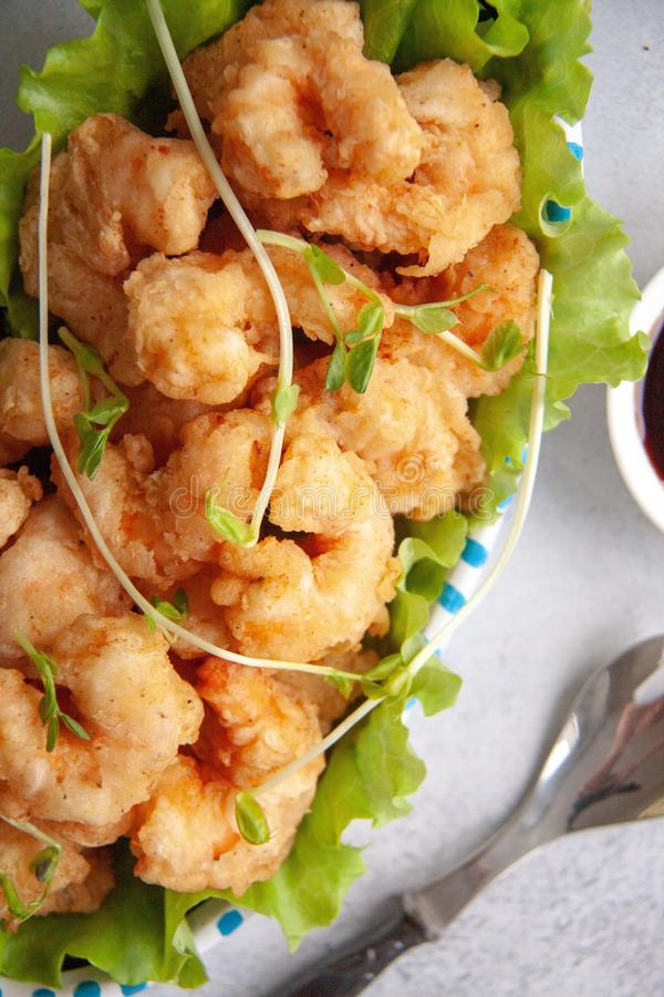 Breaded shrimp. Grilled breaded king prawns on a fresh green salad leaf royalty free stock photography