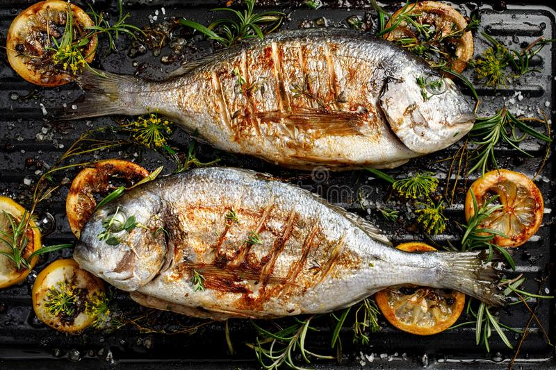 Grilled bream fish, dorada fish with the addition of spices, herbs and lemon on the grill barbecue. Top view stock photos
