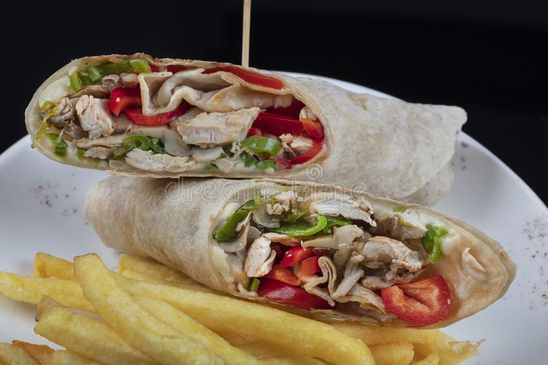 Grilled buffalo chicken sandwich wrap with romaine lettuce bleu cheese and fries stock image