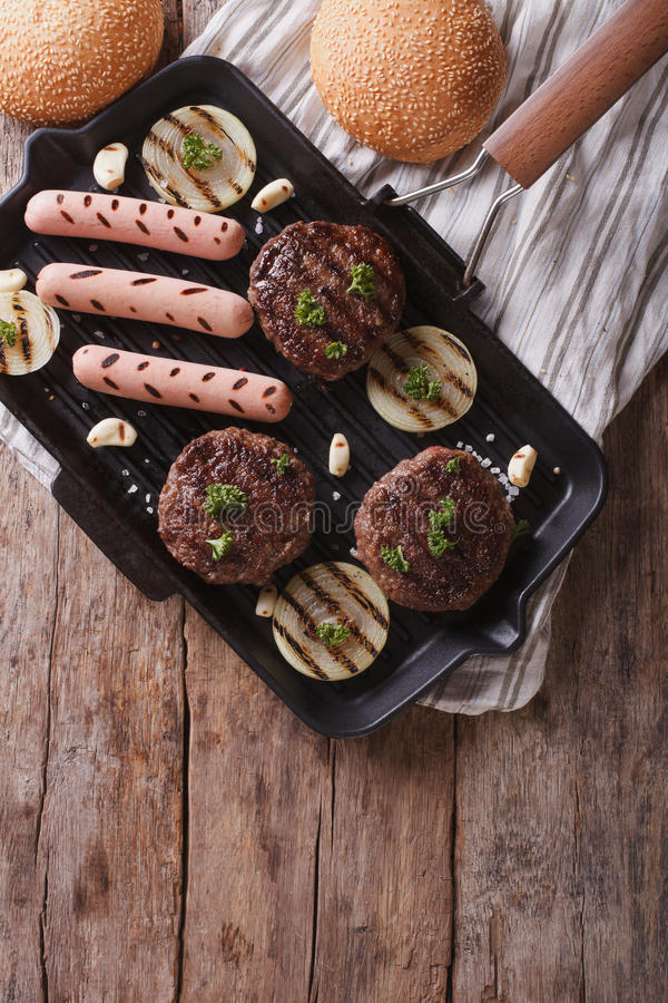 Grilled burgers and hot dogs on the grill pan. vertical top view. Grilled hamburgers and hot dogs on the grill pan. vertical top view royalty free stock photography