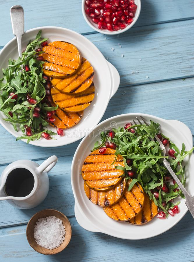 Grilled butternut squash, arugula and pomegranate salad on a blue wooden table, top view. Clean, organic, seasonal, vegetarian foo royalty free stock photo