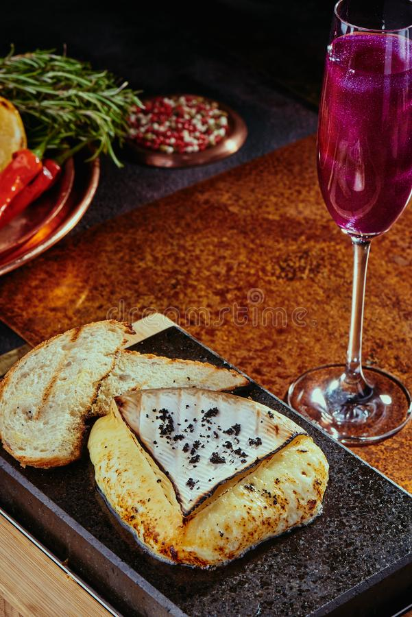 Grilled Camembert Cheese on a black square stone plate with a pink cocktail with glitter on a copper background stock photography