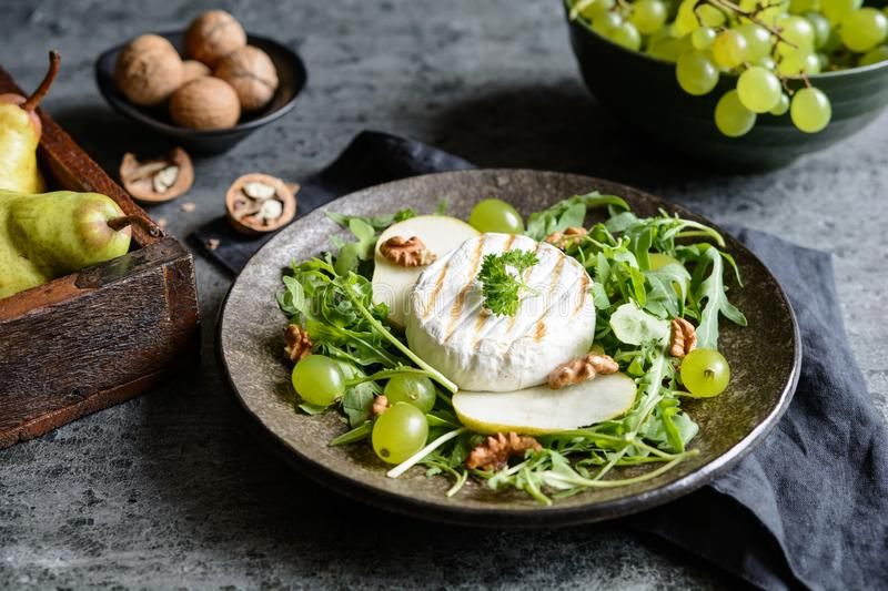 Grilled Camembert cheese with fresh arugula, green grapes, pears and walnut stock image