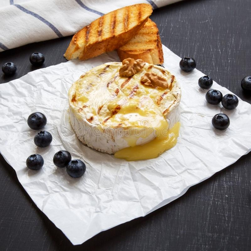 Grilled camembert cheese in paper with toasts, blueberries and walnuts on a black background, low angle view. Close-up royalty free stock images