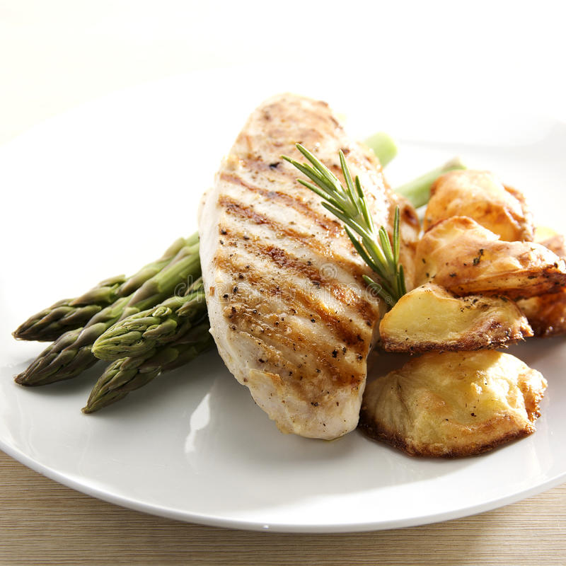 Grilled Chicken. Breast fillet with asparagus and roasted potatoes royalty free stock image