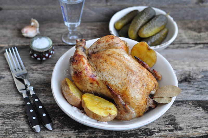 Grilled chicken with baked potato on a wooden table. Grilled chicken, baked potato on a wooden table stock photography