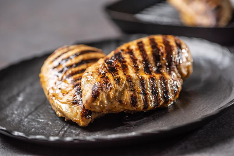 Grilled chicken breast in black plate on kitchen table royalty free stock photo