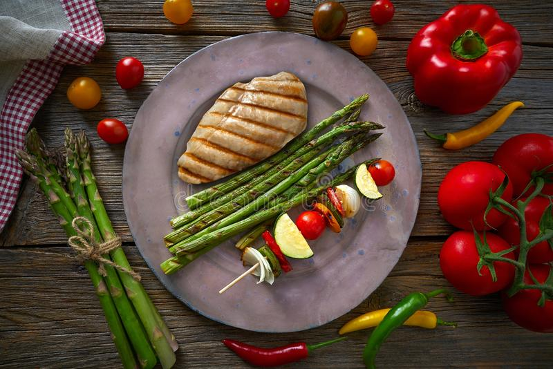 Grilled chicken breast with brochette vegetable. With grill asparagus stock images