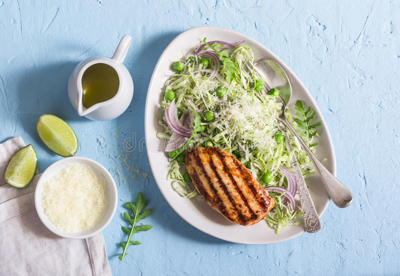 Grilled chicken breast and cabbage, green pea and parmesan coleslaw. Healthy balanced food. On a blue background. Top view stock photography