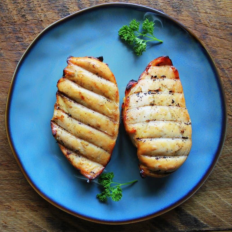 Grilled chicken breast on dark wooden background stock photography