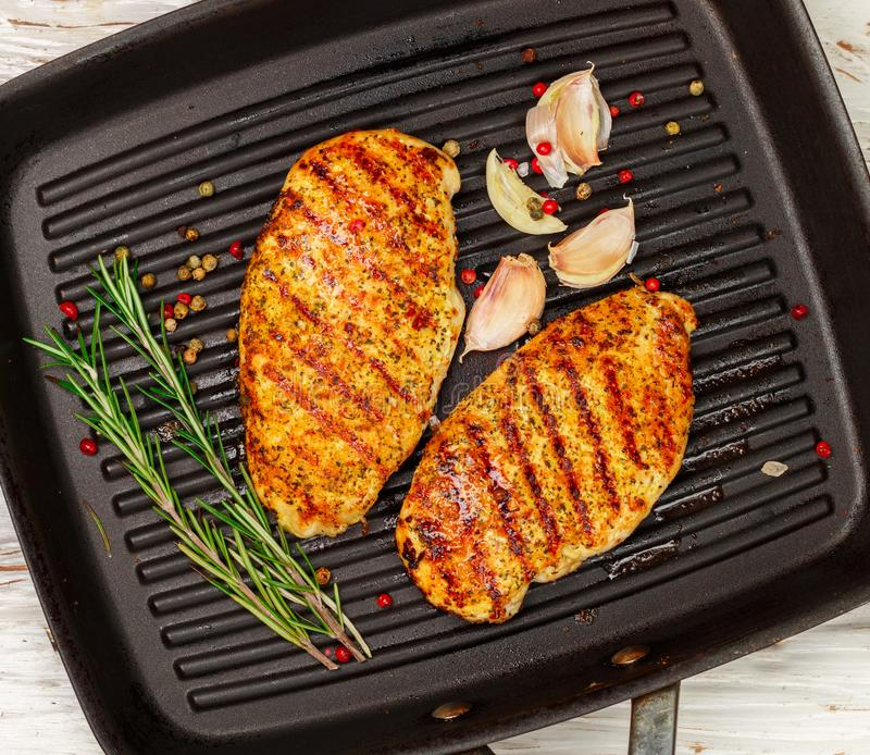 Grilled chicken breast fillet with garlic, herbs rosemary, pepper peas on the grill pan stock image