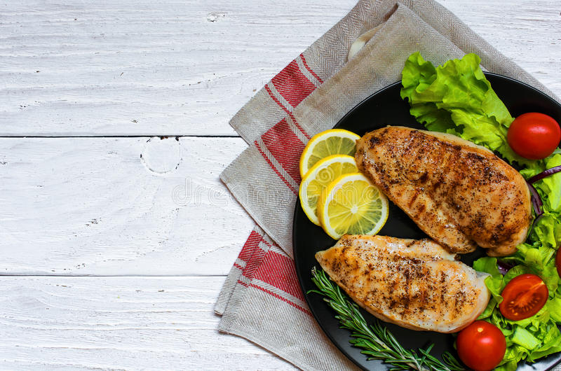 Grilled chicken breast fillet served with fresh vegetables and h stock photo
