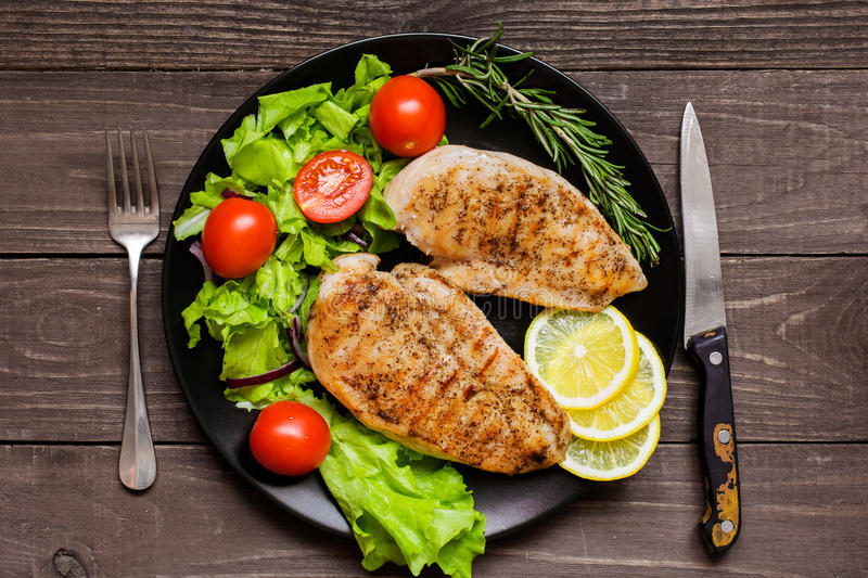 Grilled chicken breast fillet served with herbs, vegetables and stock photo