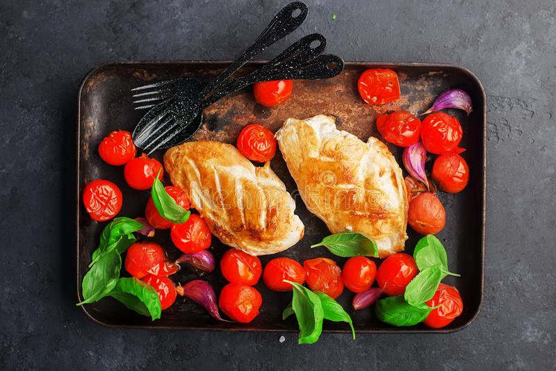 Grilled chicken breast fillet with young garlic, cherry tomatoes on a baking sheet with basil leaves. Geared dish on a stock photo