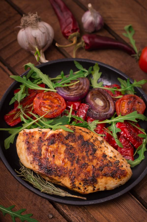 Grilled chicken breast with green salad from arugula and vegetables on a black pan. Wooden rustic background. Top view stock photos