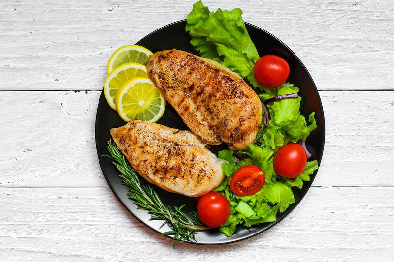grilled chicken breast with green salad, tomatoes, lemon and rosemary stock image