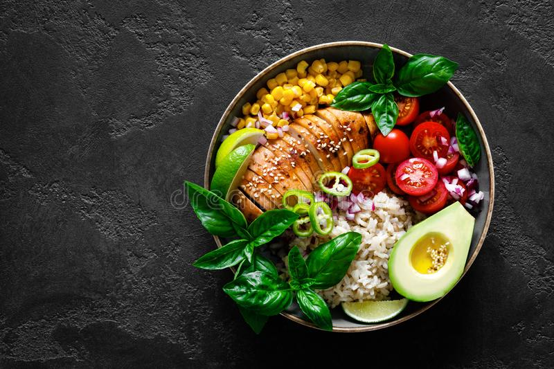 Grilled chicken breast lunch bowl with fresh tomato, avocado, corn, red onion, rice and basil royalty free stock photos