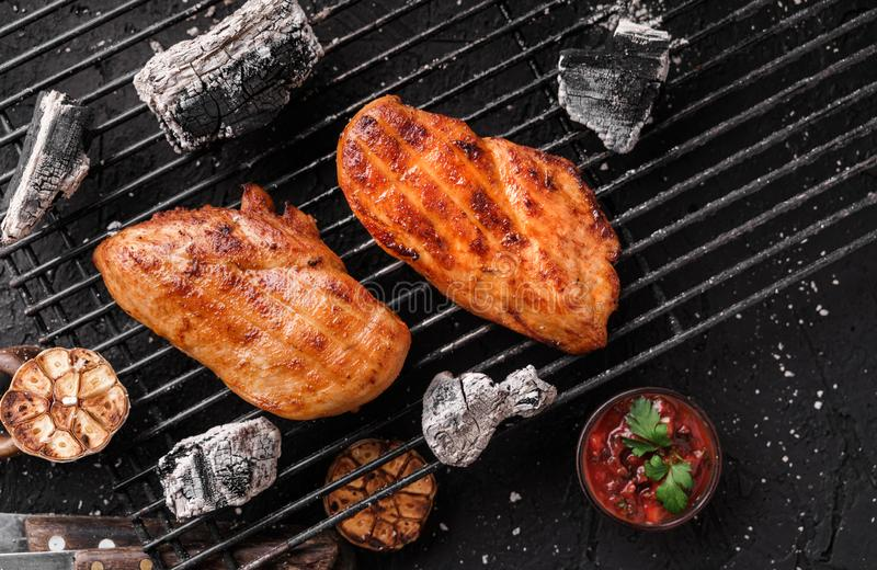 Grilled chicken breast meat with garlic over the coals on a barbecue, dark background with light of fire. Top view royalty free stock images