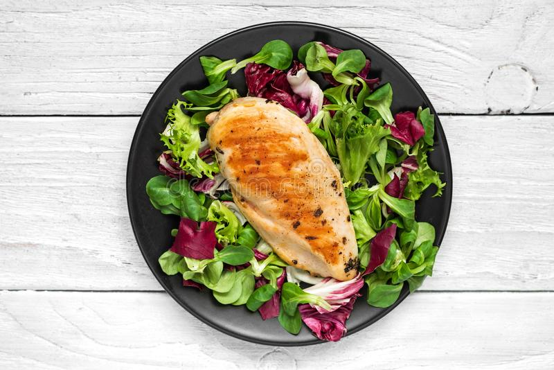 Grilled chicken breast with mixed salad on a black plate stock photography