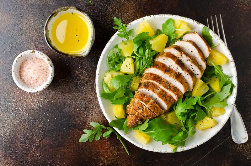 Grilled chicken breast with pineapple and arugula royalty free stock images
