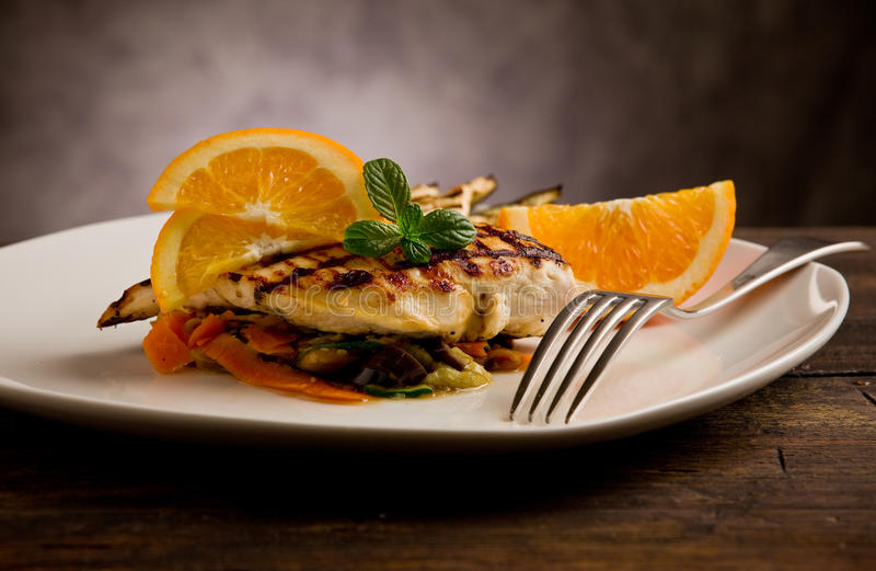 Grilled chicken breast on ratatouille bed. Delicious grilled chicken breast with orange on ratatouille bed stock photos