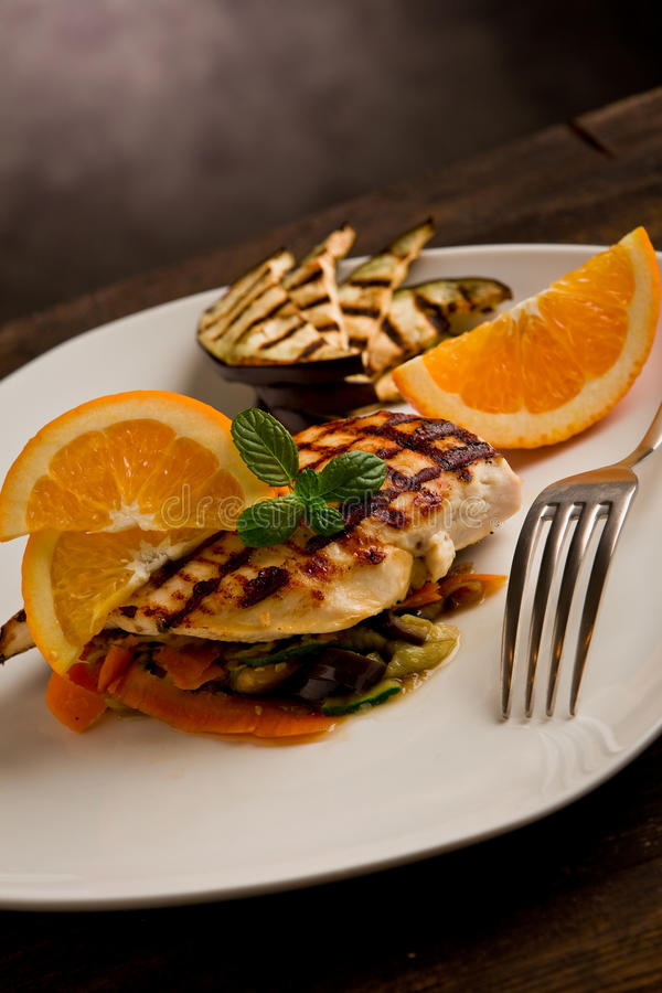 Grilled chicken breast on ratatouille bed. Delicious grilled chicken breast with orange on ratatouille bed stock image