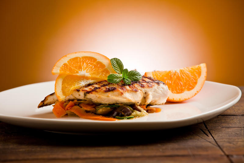 Grilled chicken breast on ratatouille bed. Delicious grilled chicken breast with orange on ratatouille bed stock images