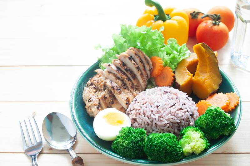 Grilled chicken breast, rice berry, broccoli, boiled egg, pumpkin and carrot. Healthy food on white background. Fitness and Diet stock image