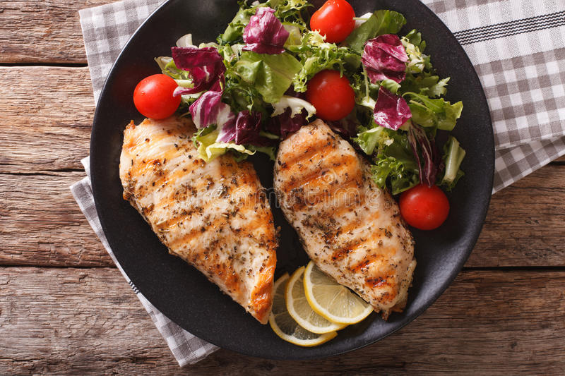 Grilled chicken breast with salad of chicory, tomatoes and lettuce close-up. horizontal top view royalty free stock photos