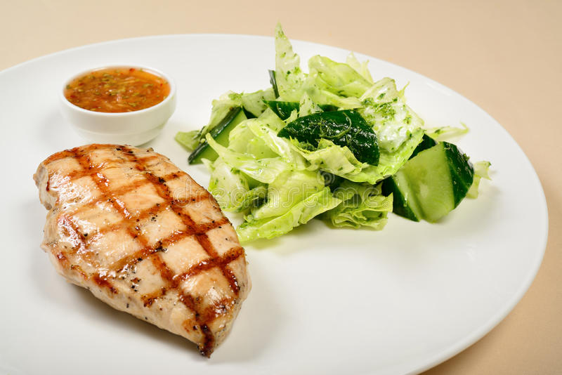 Grilled chicken breast. With salad and sauce stock photo