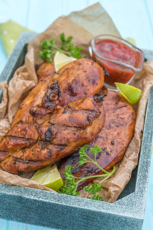 Grilled chicken breast served with herbs and lime stock images
