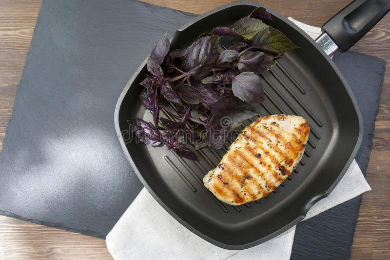 Grilled chicken breast steak with violet basil on teflon pan grill royalty free stock images