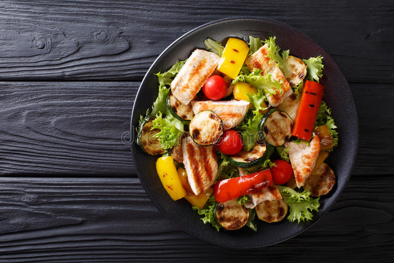 Grilled chicken breast and summer vegetables close-up on a plate royalty free stock photography