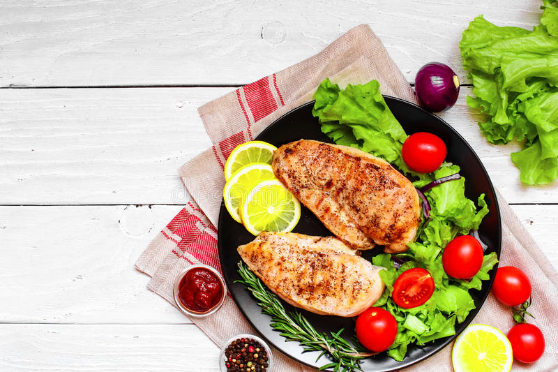 Grilled chicken breast with vegetables and herbs stock photos