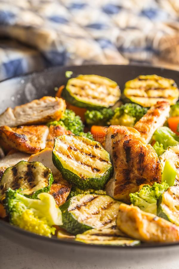 Grilled chicken breast zucchini broccoli and carrot in black plate. Greek or mediterranean food stock photos