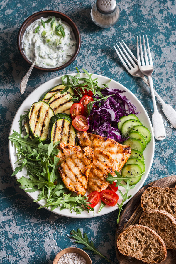 Grilled chicken breast, zucchini and garden vegetable bowl. Healthy diet food concept, top view. Delicious healthy lunch stock images
